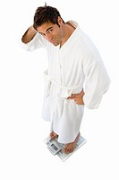 Young man standing in robe on weighing scales, cut out (thumbnail)
