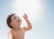 Mixed race boy pointing to the sky
