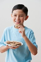 Mixed race boy eating cookies