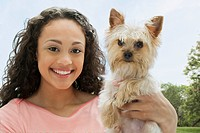 Mixed race teenage girl holding dog