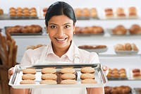 Indian woman holding cookies in bakery
