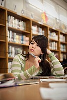 Mixed race teenage girl daydreaming in school library