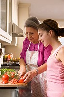 Hispanic grandmother and granddaughter cutting vegetables