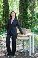 Hispanic businesswoman with desk in forest