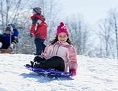 Girl riding downhill on sled