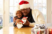 African grandfather and grandson wearing Santa hats eating Christmas cookies
