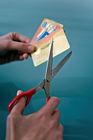 Hands cutting credit cards with scissors