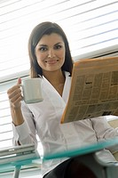 Professional woman with newspaper and coffee cup (thumbnail)