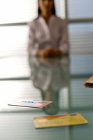 Professional woman in background of credit cards on desk
