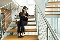 Businesswoman telephoning from cell phone on office staircase