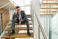 Businessman on office staircase holding his head (thumbnail)