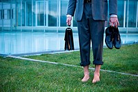 Businessman from waist down barefoot on grass outside of office building