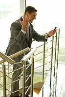 Happy businessman on staircase looking at cell phone