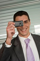 Businessman photographing with cell phone camera