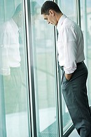 Businessman looking out the window, hand in pocket