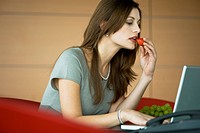 Businesswoman eating a strawberry at laptop (thumbnail)