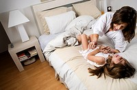 Young woman and girl on bed laughing