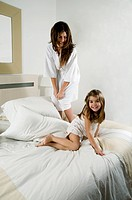 Young woman and girl on bed playing