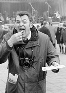 Sixties, black and white photo, people, humour, man with a camera and wide opened mouth bites into a frying sausage and makes faces, aged 30 to 35 yea...