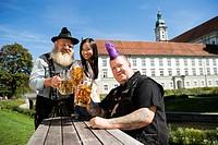 Germany, Bavaria, Upper Bavaria, Three people in beer garden holding beer stein glasses, smiling