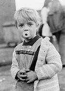 Seventies, black and white photo, people, children, little girl, portrait, street kid, running nose, dirty, mucky, baby_soother in the mound, aged 4 t...