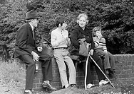 Seventies, black and white photo, people, grandparents and two grandchildren take a walk, sitting on a wall and have a rest with a small picnic, grand...