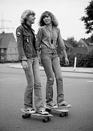 Seventies, black and white photo, people, two young girls on rollerblades drive on the street, jeans suit, jeans trousers, aged 15 to 18 years