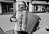 Eighties, black and white photo, people, homeless man stands in a pedestrian zone and plays on a accordion, aged 50 to 70 years
