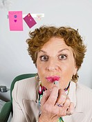 Woman applying lipstick in office