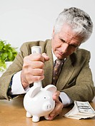 Man trying to put banknotes in piggy bank