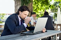 Germany, Bavaria, Upper Bavaria, Young business man in beer garden drinking beer