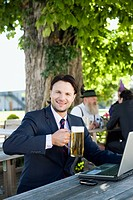 Germany, Bavaria, Upper Bavaria, Young businessman in beergarden holding beer stein, smiling, portrait