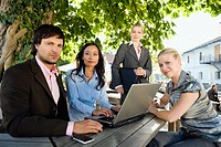 Germany, Bavaria, Upper Bavaria, Business people using laptop in beer garden
