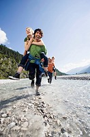 Germany, Bavaria, Tölzer Land, Men carrying young women piggyback
