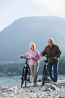 Germany, Bavaria, Walchensee, Senior couple pushing bikes across lakeshore