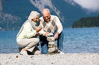 Germany, Bavaria, Walchensee, Senior couple piling up stones