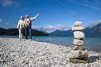 Germany, Bavaria, Walchensee, Senior couple taking a walk, stone pyramid in foreground