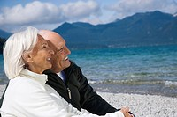 Germany, Bavaria, Walchensee, Senior couple relaxing on lakeshore