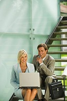 Germany, two business people sitting on stairs, woman using laptop