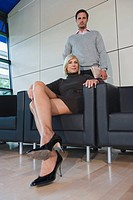 Germany, two business people, woman sitting in armchair