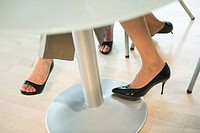 Germany, women´s feet below table, low section