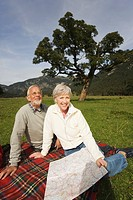 Austria, Karwendel, Senior couple with map sitting in meadow