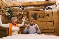 Senior couple throwing playing cards into air