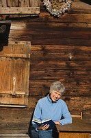 Austria, Senior woman reading book by log cabin