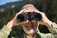 Austria, Karwendel, Senior man looking through binocular, portrait