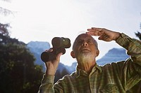 Austria, Karwendel, Senior man holding binocular, looking up
