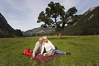 Austria, Karwendel, Senior couple sitting in meadow looking at map
