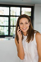 Young woman in office using mobile phone, smiling, portrait
