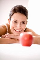 Young woman looking at apple, smiling