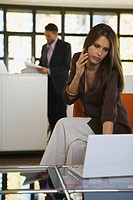 Young woman in office using mobile phone, man in background